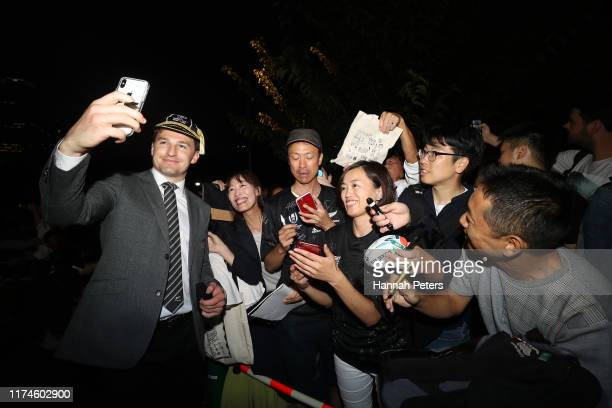 Beauden Barrett of the All Blacks signs autographs for fans during a New Zealand All Blacks Rugby World Cup Welcome Ceremony at Zojoji Temple on...