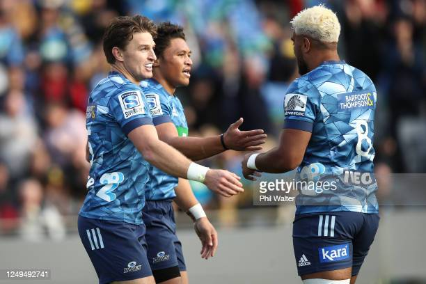 Beauden Barrett of the Blues congratulates Caleb Clarke on his try with Hoskins Sotutu during the round 1 Super Rugby Aotearoa match between the...