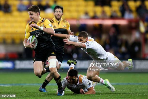 Beauden Barrett of the Hurricanes beats the tackles of Anton LienertBrown and Tawera KerrBarlow of the Chiefs during the round 16 Super Rugby match...