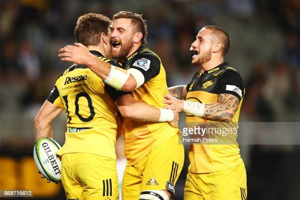 Beauden Barrett of the Hurricanes celebrates with Callum Gibbins and TJ Perenara after scoring a try during the round eight Super Rugby match between...