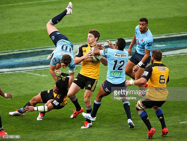 Beauden Barrett of the Hurricanes gathers a loose ball while Bernard Foley of the Waratahs collides with Ma'a Nonu during the round 10 Super Rugby...