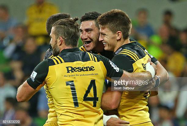 Beauden Barrett of the Hurricanes is congratulated by Cory Jane and his teammates after scoring a try during the round eight Super Rugby match...