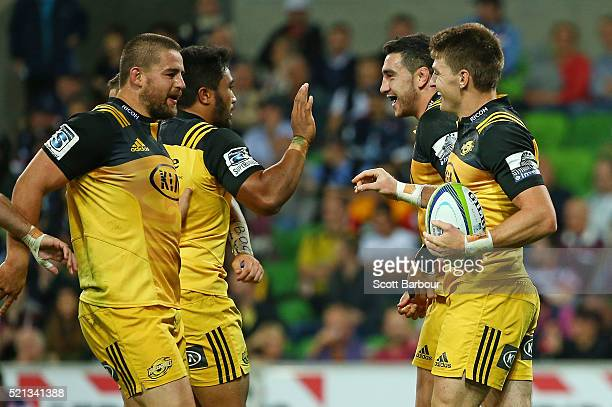 Beauden Barrett of the Hurricanes is congratulated by Dane Coles and his teammates after scoring a try during the round eight Super Rugby match...