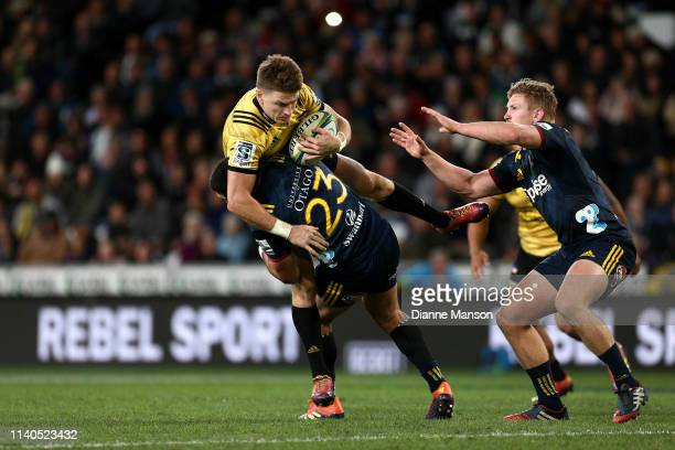 Beauden Barrett of the Hurricanes is tackled by Rob Thompson of the Highlanders during the round 8 Super Rugby match between the Highlanders and...