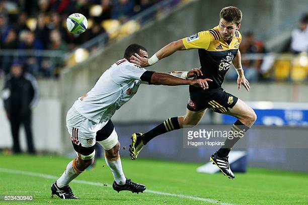 Beauden Barrett of the Hurricanes keeps the ball in play under pressure from Michael Leitch of the Chiefs during the round nine Super Rugby match...