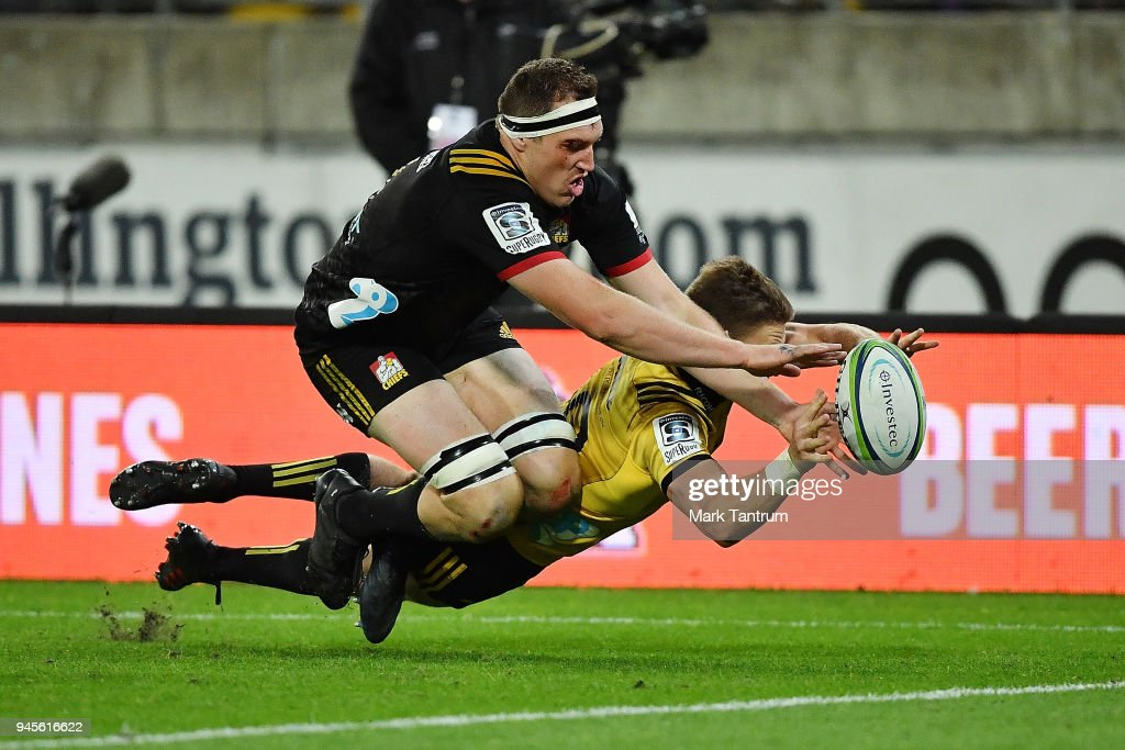 Beauden Barrett of the Hurricanes scores against Brodie Retallick of the Chiefs during the round nine Super Rugby match between the Hurricanes and the Chiefs at Westpac Stadium on April 13, 2018 in Wellington, New Zealand.