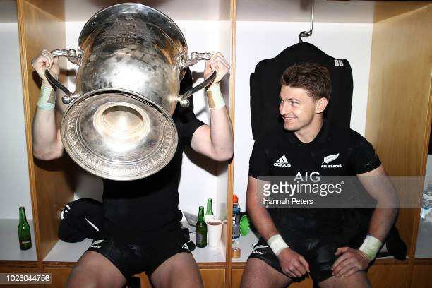 Beauden Barrett watches Jordie Barrett drink from the Bledisloe Cup in the dressing room after winning The Rugby Championship game between the New...