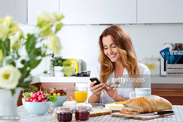 Beauiful woman using smart phone during breakfast