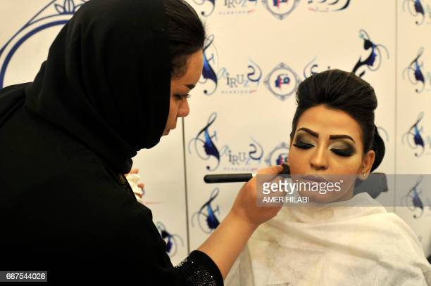 A beautician applies makeup on a Saudi woman at a bridal expo on April 11 in the Red Sea city of Jeddah / AFP PHOTO / Amer HILABI