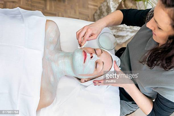 Beautician Applying Mask on Pretty Woman's Face and Cleavage, Europe