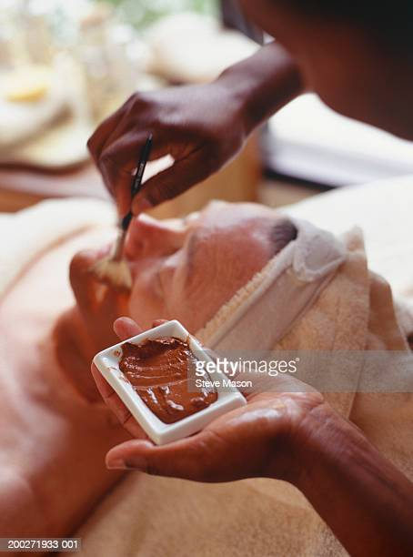 beautician applying mud mixture to clients face on treatment table - beauty care occupation stock photos and pictures