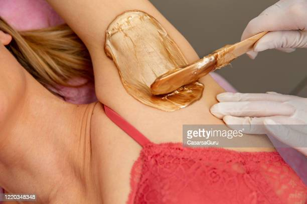 beautician applying wax on woman's armpit - stock photo - wax stock pictures, royalty-free photos & images