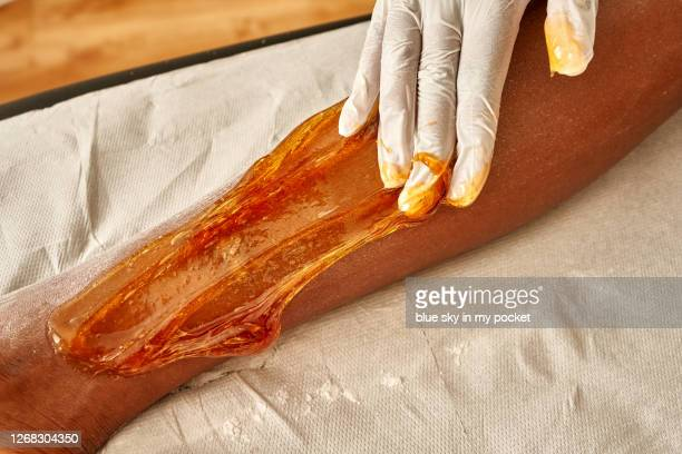 a beautician at work on a clients legs - leg waxing stock pictures, royalty-free photos & images