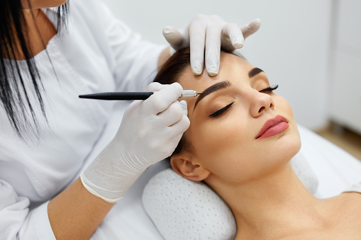 Beautician Doing Permanent Eyebrows Makeup Tattoo On Woman Face 952772504