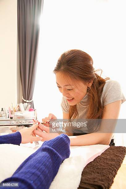 A beautician is polishing nails.