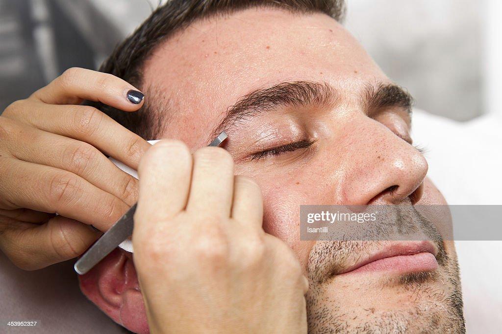 Beautician plucking a beautiful man eyebrows with tweezers : Stock Photo