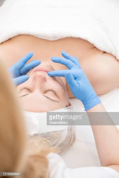 beautician préparant la peau de la femme pour le traitement facial - photo stock - vaseline photos et images de collection
