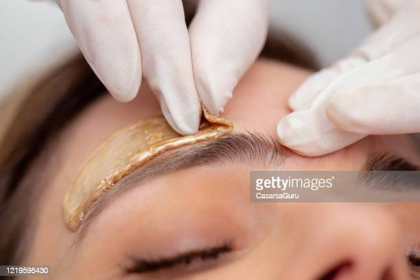 beautician removing eyebrow hairs with wax - stock photo - wax stock pictures, royalty-free photos & images
