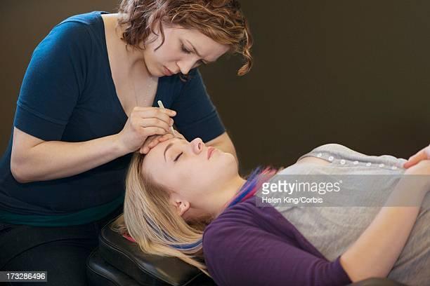 beautician tweezing customer's eyebrows - estetista foto e immagini stock
