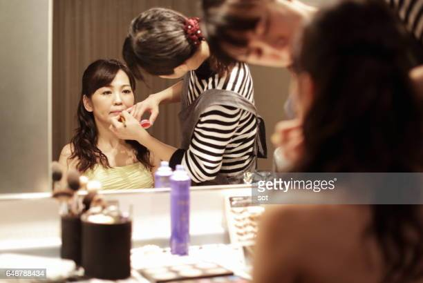 Beautician using lipstick on a woman in front of mirror