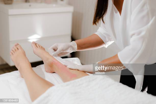beautician waxing a woman's leg - waxing hair removal stock pictures, royalty-free photos & images