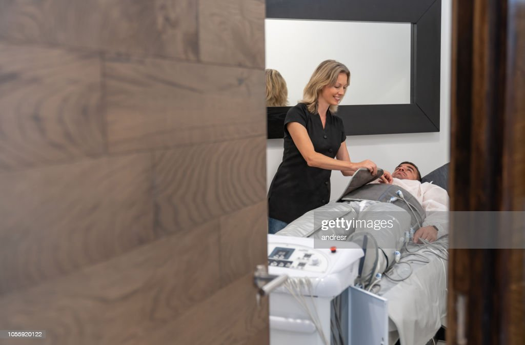 Beautician working at a spa doing a pressotherapy session to a woman : Stock Photo