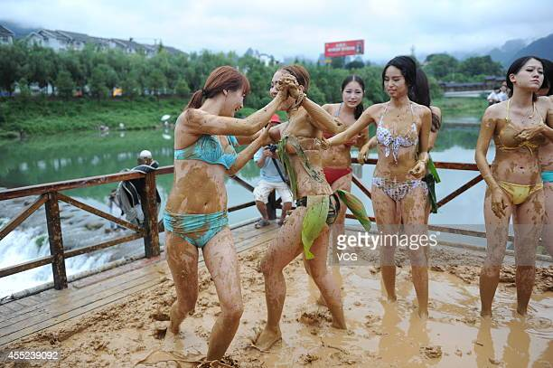 Beauties wearing bikini participate in a mud competition on September 10 2014 in Zhangjiajie Hunan Province of China