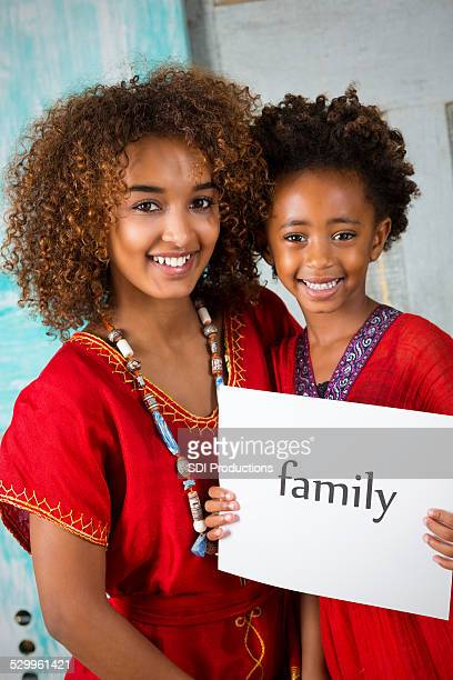 Beautifu adopted Ethiopian sisters in traditional clothing holding FAMILY sign