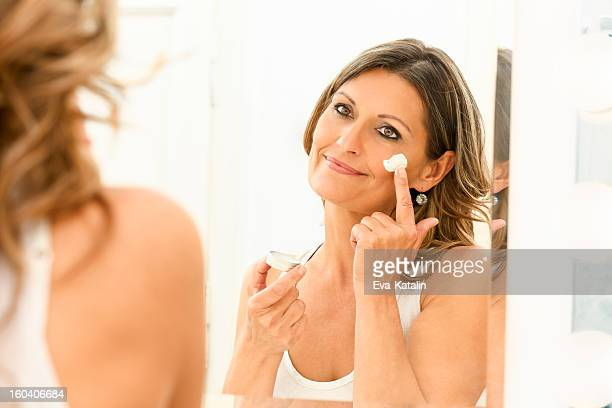 beautiful 40s woman applying moisturizer - 40 49 years stock pictures, royalty-free photos & images