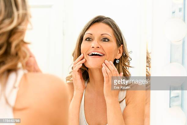 Beautiful 40s woman looking at herself in a mirror