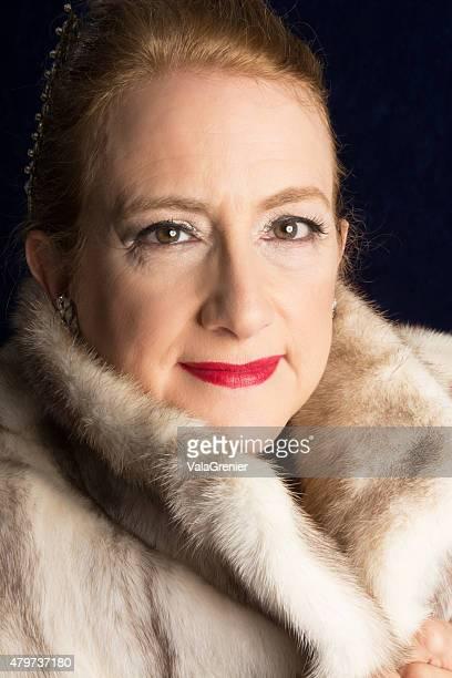 Beautiful 55 year old woman in fur coat, hair back.