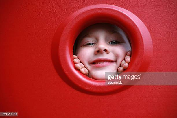 A beautiful 6 year-old girl peeking out at a playground.