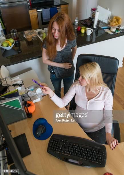Schöne aktive schwangere junge Frau in das Büro zu Hause arbeiten und unterrichten die Teenager-Mädchen