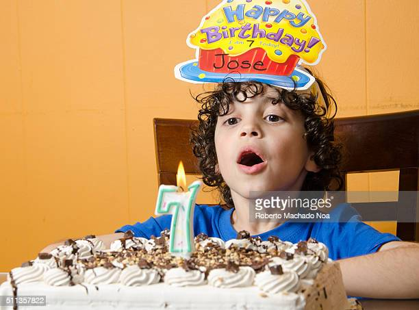 Beautiful adorable seven year old boy in blue shirt celebrating his birthday blowing candles on cake indoor Birthday party for kids