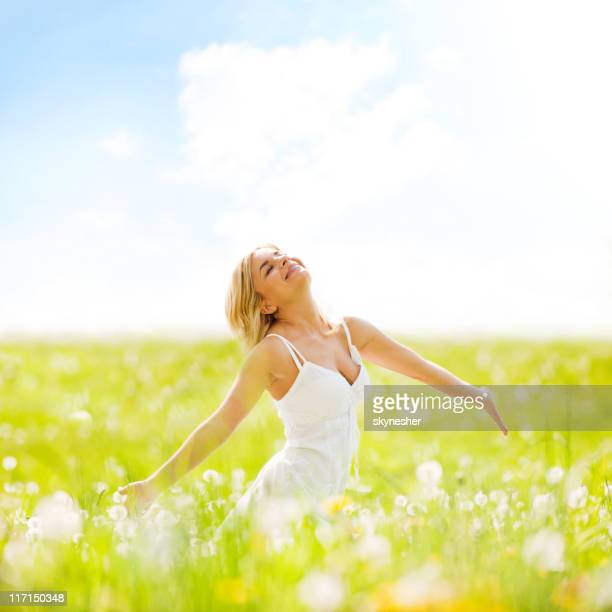 beautiful adult blonde standing on sunny field enjoying herself. - green dress stock pictures, royalty-free photos & images