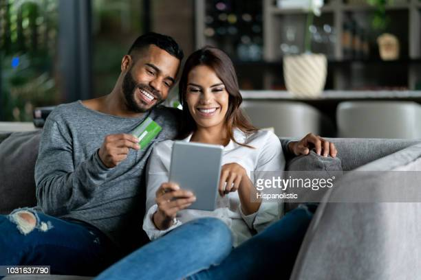 beautiful adult couple at home relaxing on couch shopping online while man holds credit card both smiling - home shopping stock pictures, royalty-free photos & images