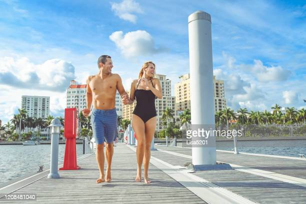 beautiful adventurous couple run down a dock in swimwear holding hands - west palm beach stock pictures, royalty-free photos & images
