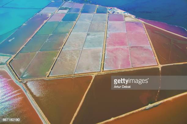 beautiful aerial picture flying over delta del ebro, a unique nature outdoor with beautiful colors and textures, with beach and colorful salt pans in the catalonia region. - delta del ebro fotografías e imágenes de stock