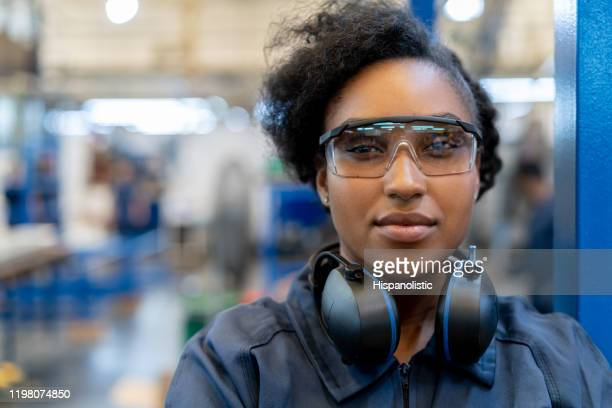 beautiful african american engineer at a factory wearing protective workwear smiling at camera - protective eyewear stock pictures, royalty-free photos & images