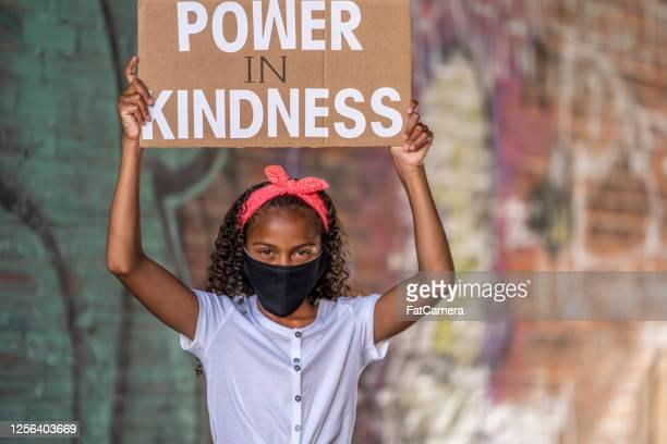 抗議の看板を持つ美しいアフリカ系アメリカ人の女の子 - social justice concept ストックフォトと画像