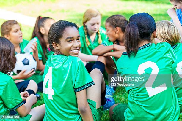 beautiful african american girl smiling with her soccer team - sporting term stock-fotos und bilder