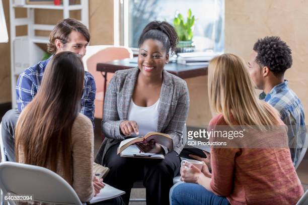 beautiful african american leads diverse bible study group - christendom stockfoto's en -beelden