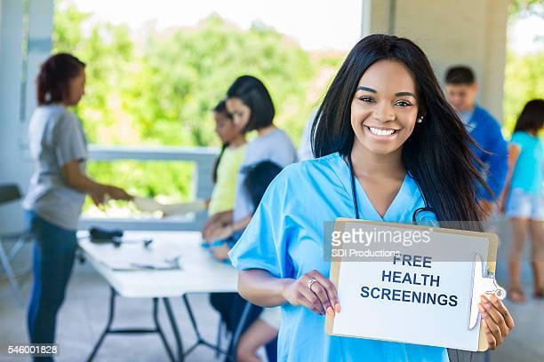 Beautiful African American Nurse holding ''Free Health Screenings'' sign