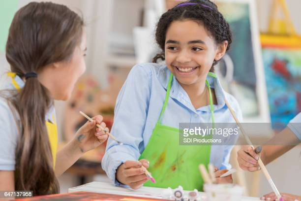 Beautiful African American preteen girls paint in art class
