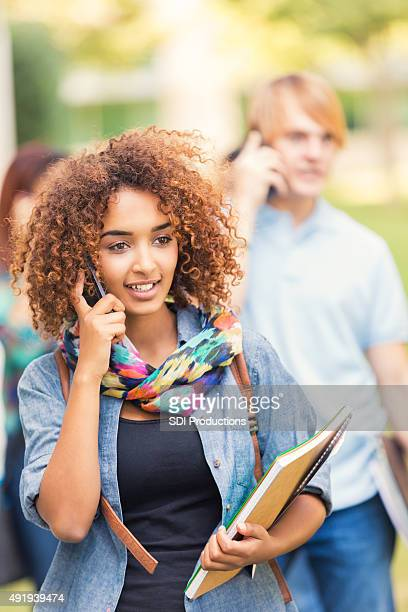 Beautiful African American student talking on cell phone at school