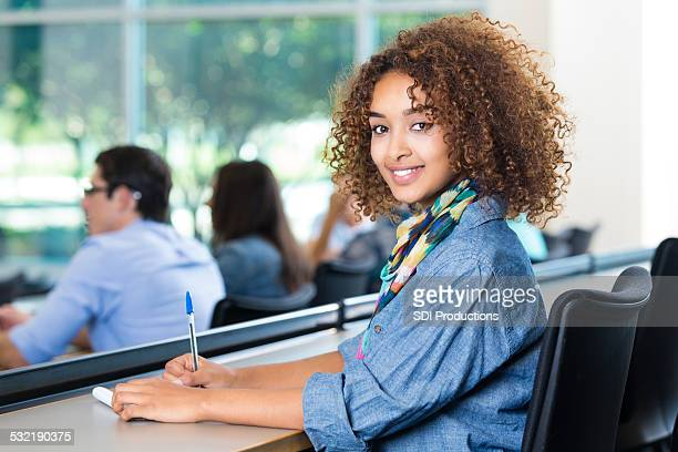 beautiful african american teen girl taking notes in college classroom - beautiful ethiopian girls stock photos and pictures