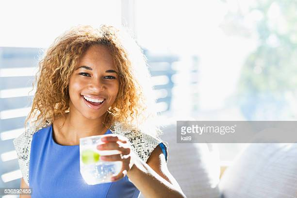 Beautiful African American teenage girl drinking water