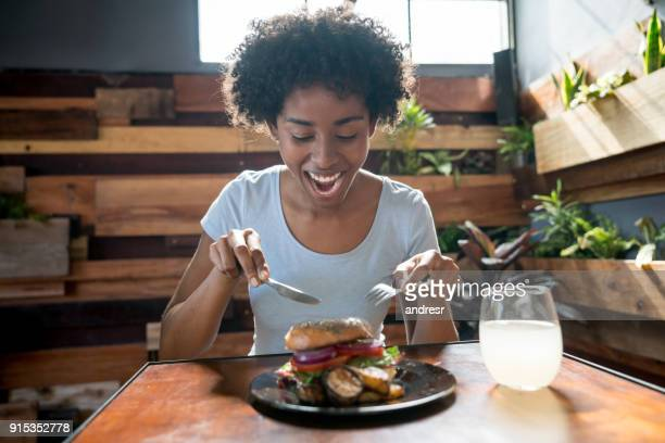Beautiful african american woman eating a delicious bagel with vegetables