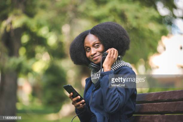 beautiful african american woman getting ready to listen to a podcast on her mobile device, in a public park - mmeemil stock photos and pictures