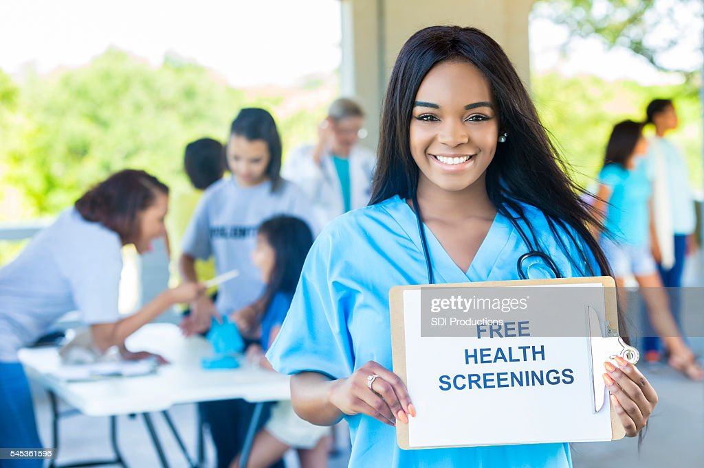 "Beautiful African American Woman holding a """"Free Health Screenings"""" sign : Stock Photo"